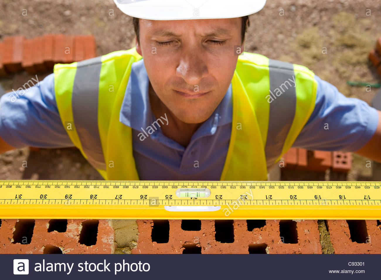 Close up of bricklayer holding carpenter rule along bricks on wall - Stock Image