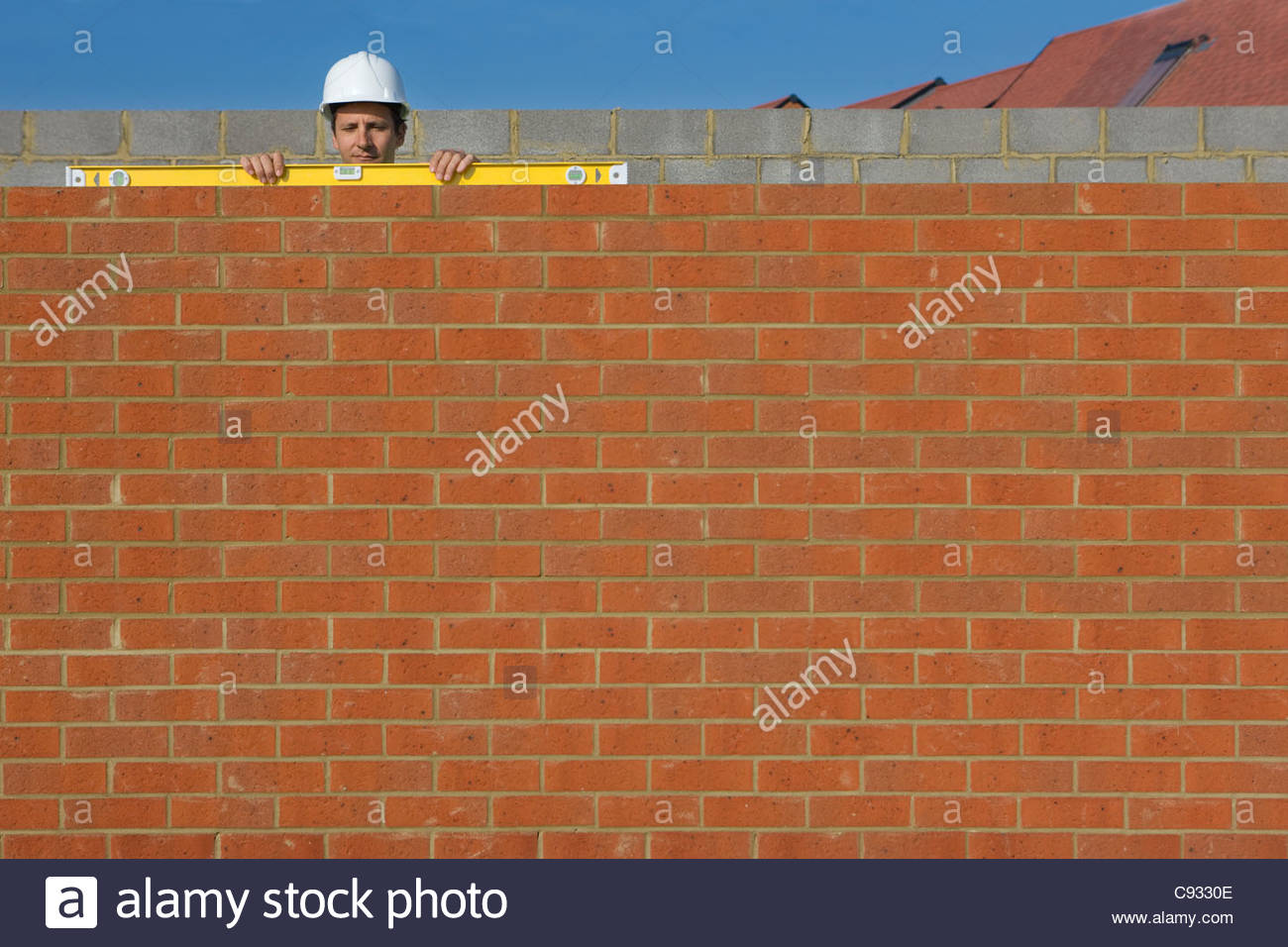 Bricklayer holding level tool on brick wall - Stock Image