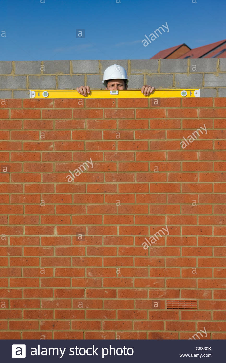 Portrait of bricklayer holding level tool on brick wall - Stock Image