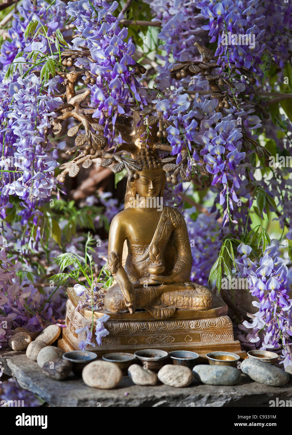 A small Buddha shrine surrounded by wisteria in the Hotel Gangtey Palace. - Stock Image