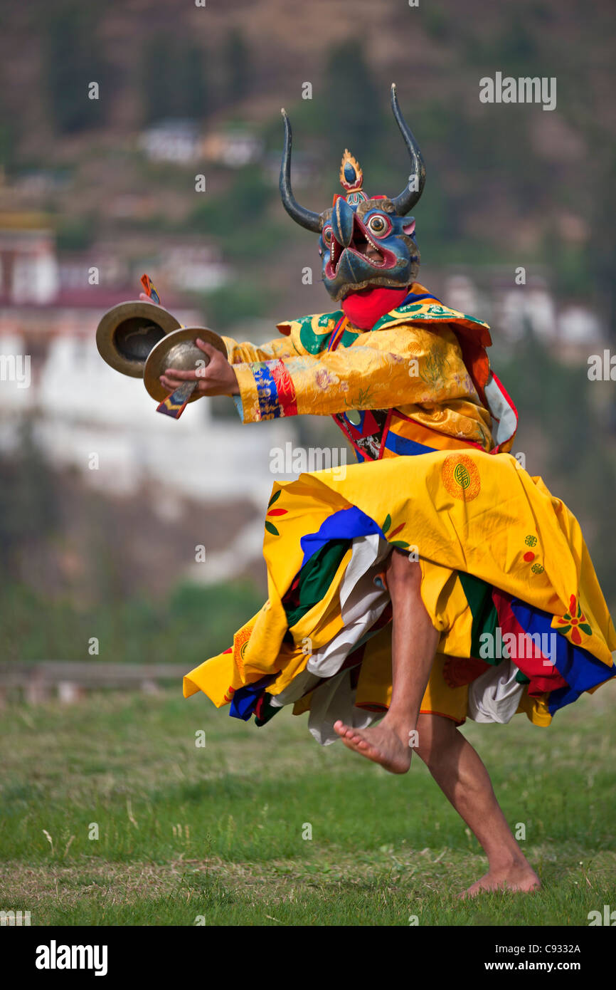 A masked dancer with cymbals performs Drametse Nga Cham. - Stock Image