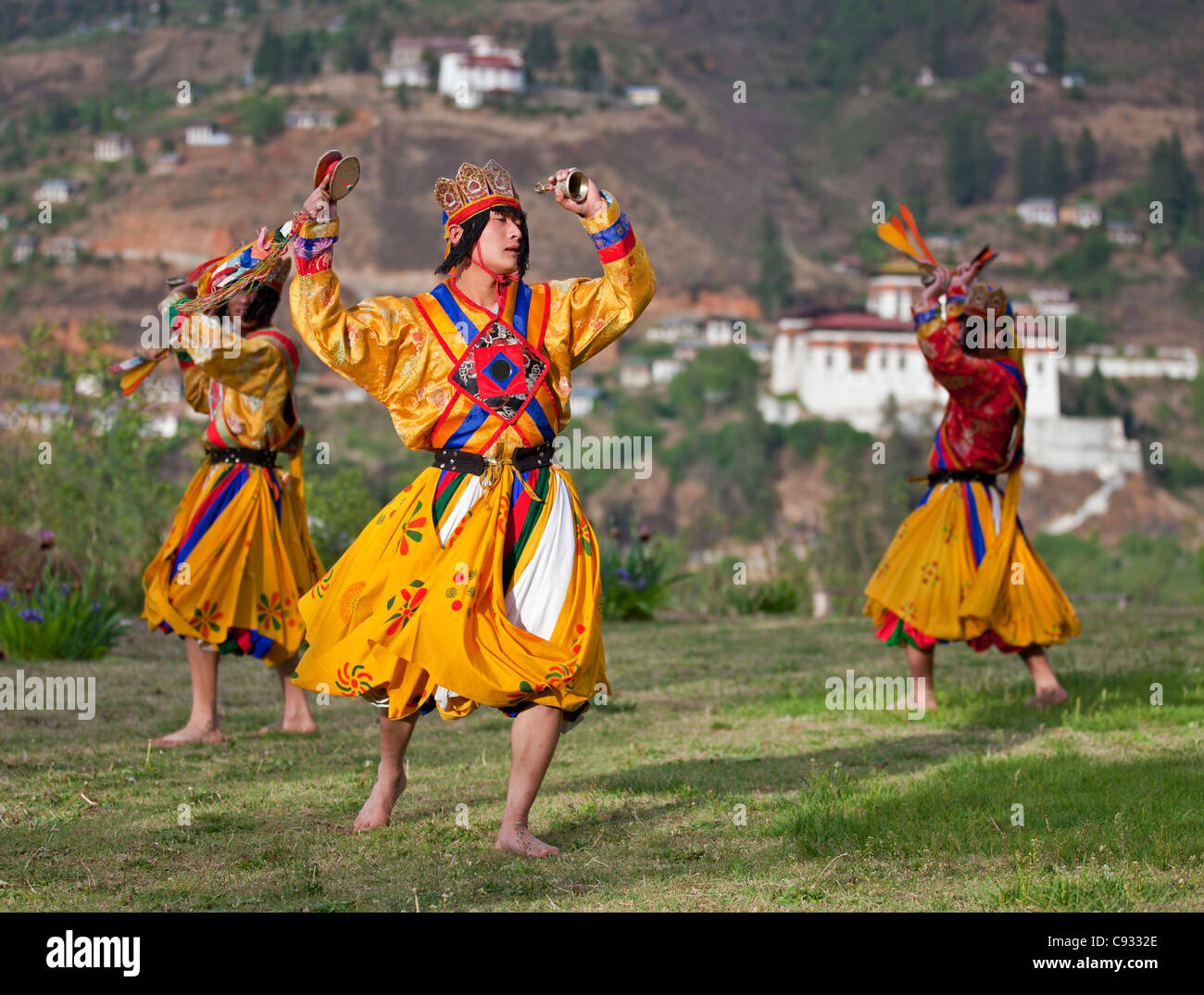 Dancers perform Pa-Cham, the Dance of the Heroes, with Paro Dzong in the background. - Stock Image