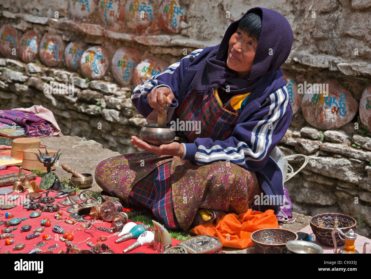 A souvenir seller waiting for tourists outside Kurjey Lhakhang, a complex of three temples. - Stock Image