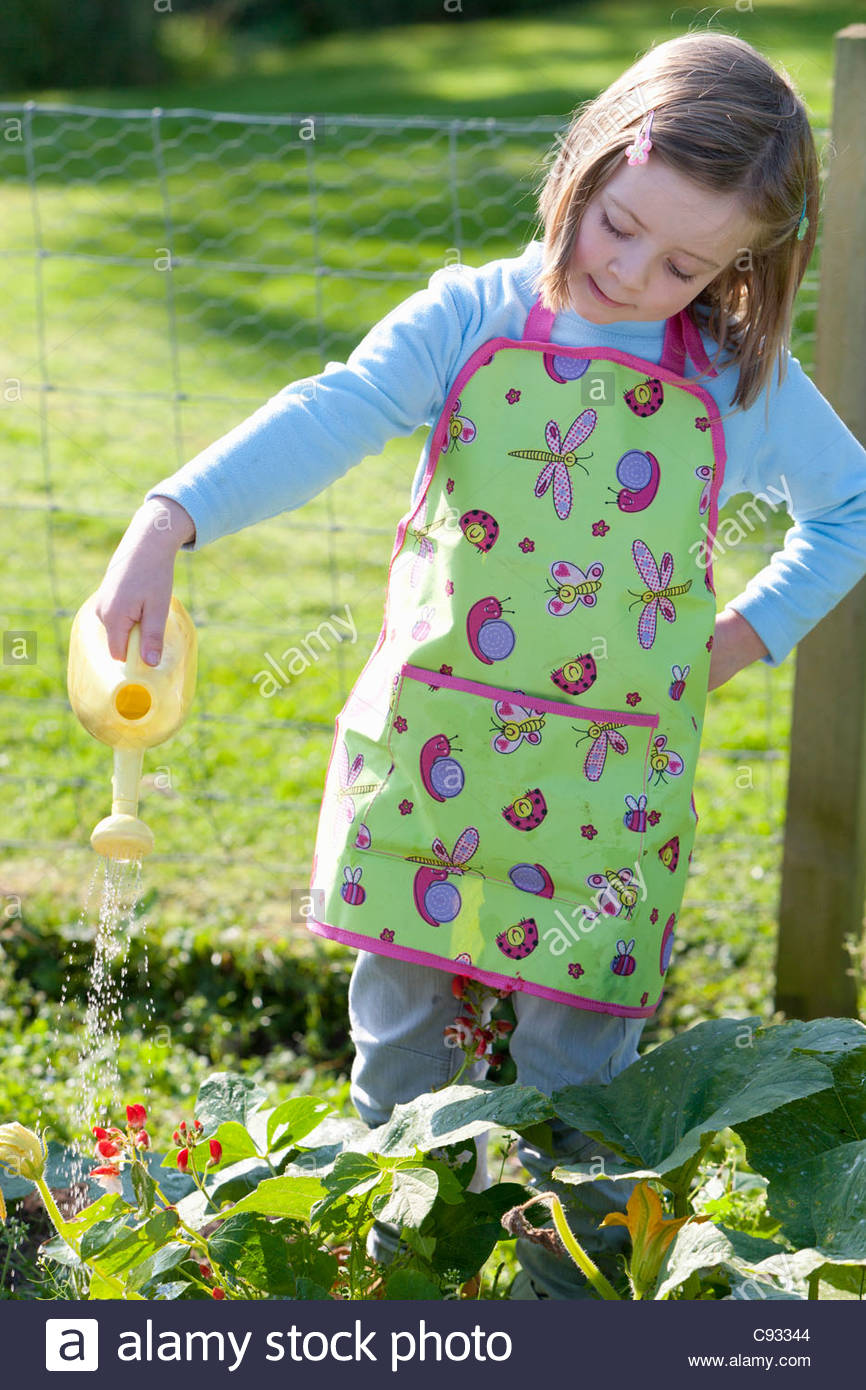Girl in apron watering plants in garden with small watering can - Stock Image