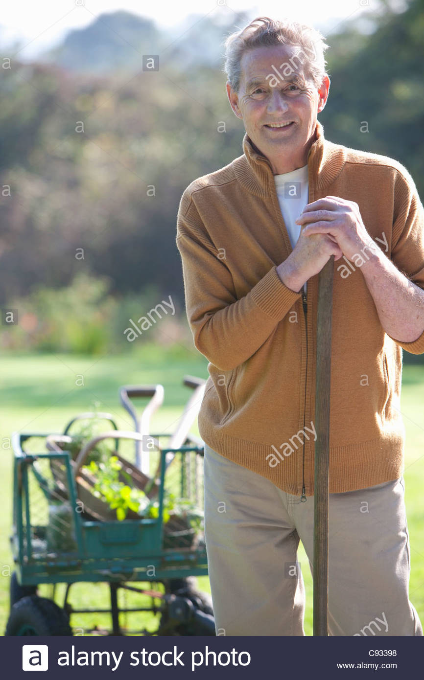 Portrait of smiling senior man with gardening tools - Stock Image