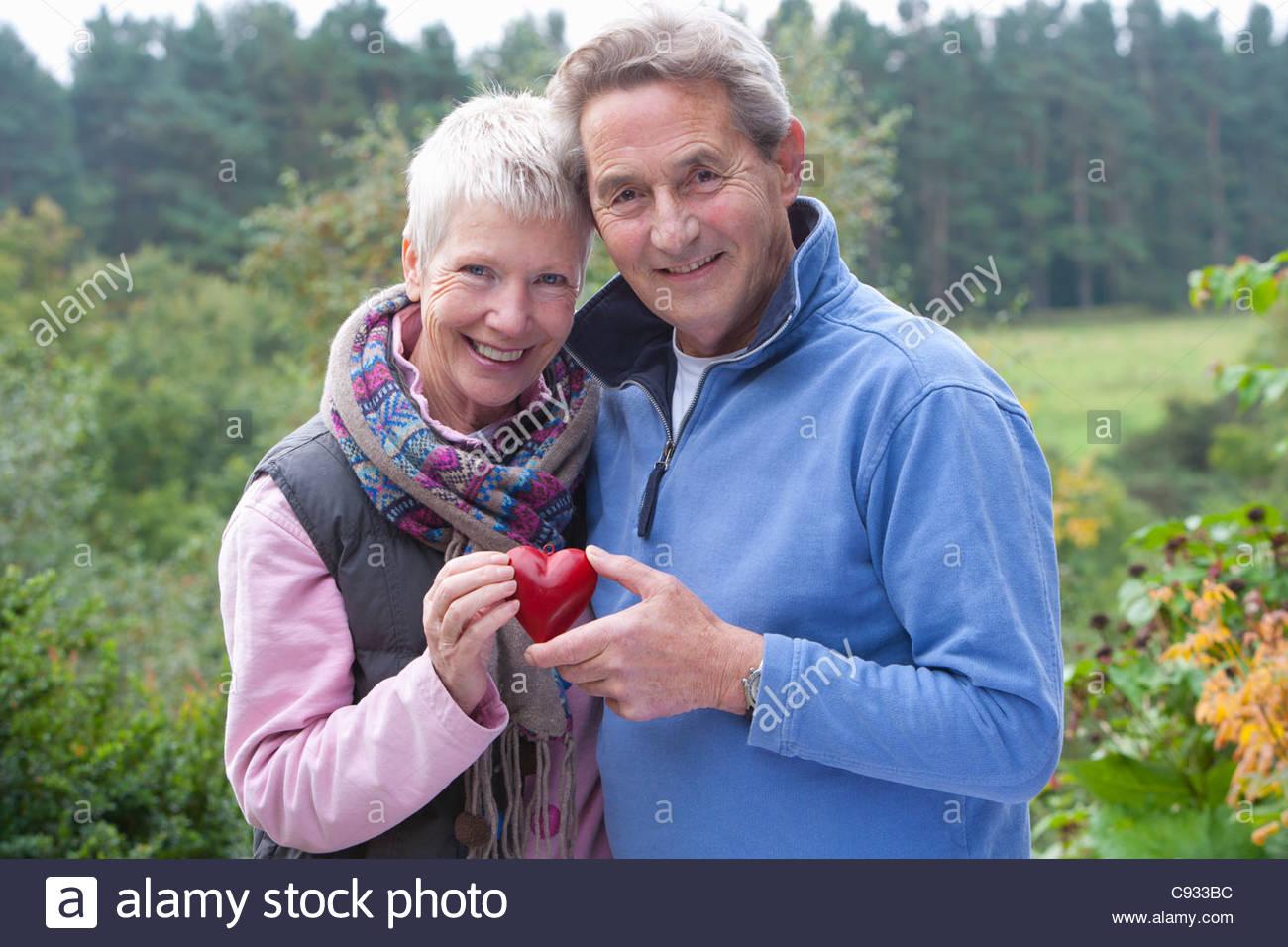 Portrait of smiling senior couple holding heart-shape ornament in garden - Stock Image