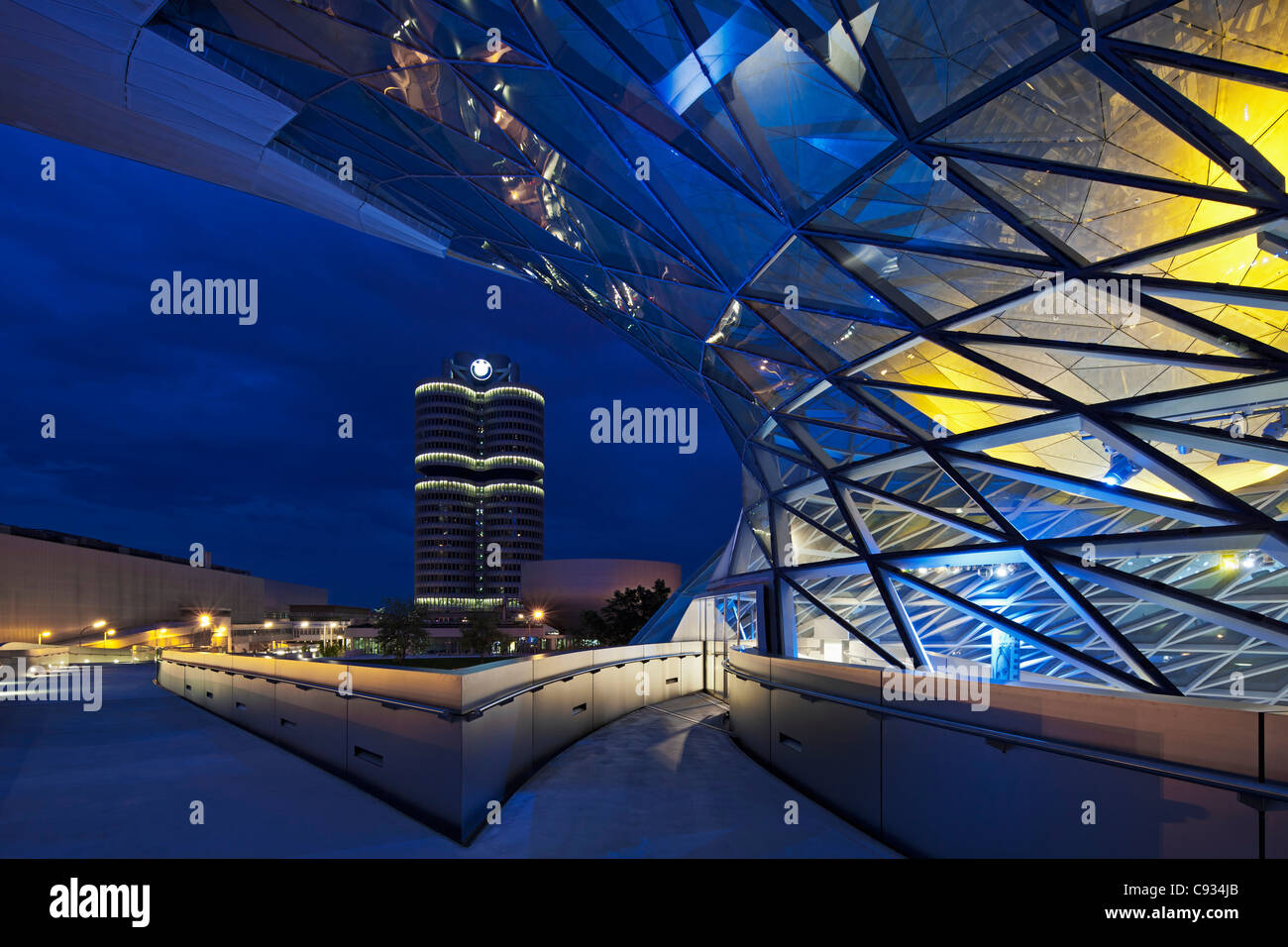 Twilight view of the pedestrian bridge link to the BMW Headquarters Office building and Museum, Munich, Bavaria, - Stock Image