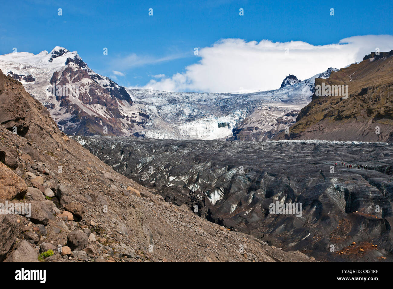 Visitors walking up Svinsfaellsjokull glacier with crampons strapped to their boots. - Stock Image