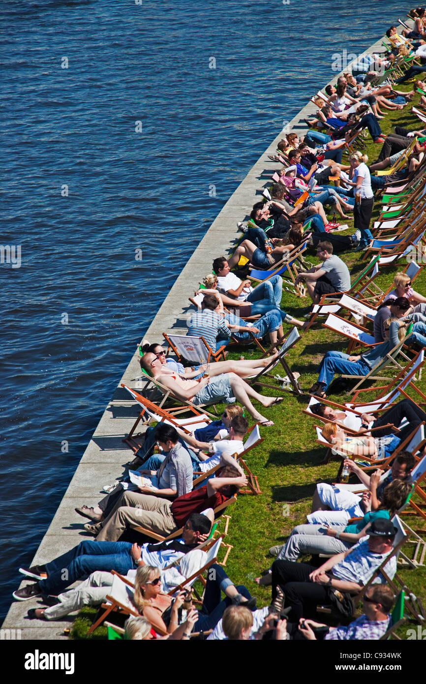 Tourists sit in deck chairs on the banks of the River Spree at the Capital Beach Strand Bar, Tiergarten, Berlin, - Stock Image