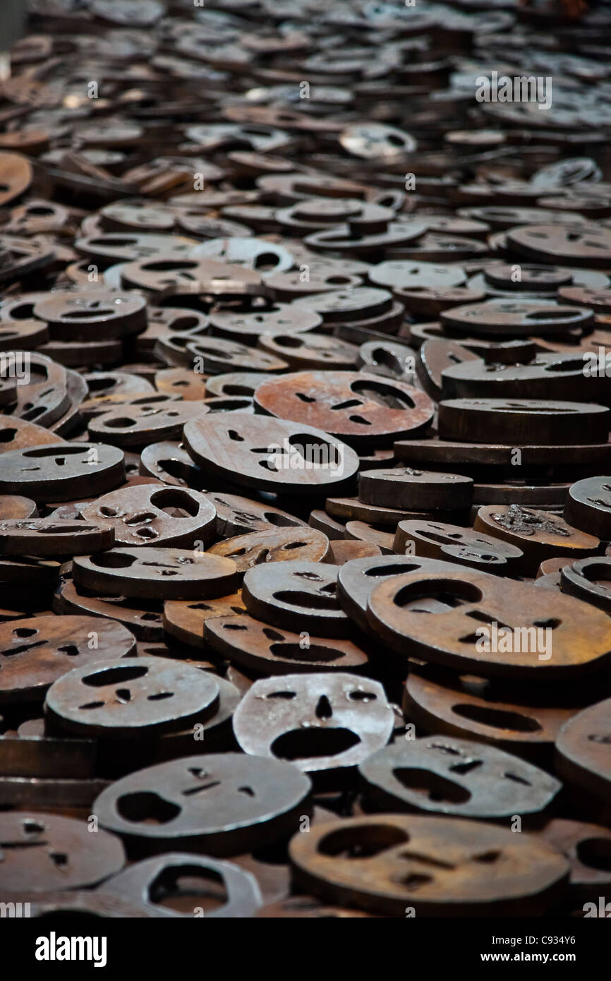 10002 open-mouthed iron plate faces cover the floor in the Jewish Museum, Berlin, Kreuzberg, Berlin, Germany. - Stock Image