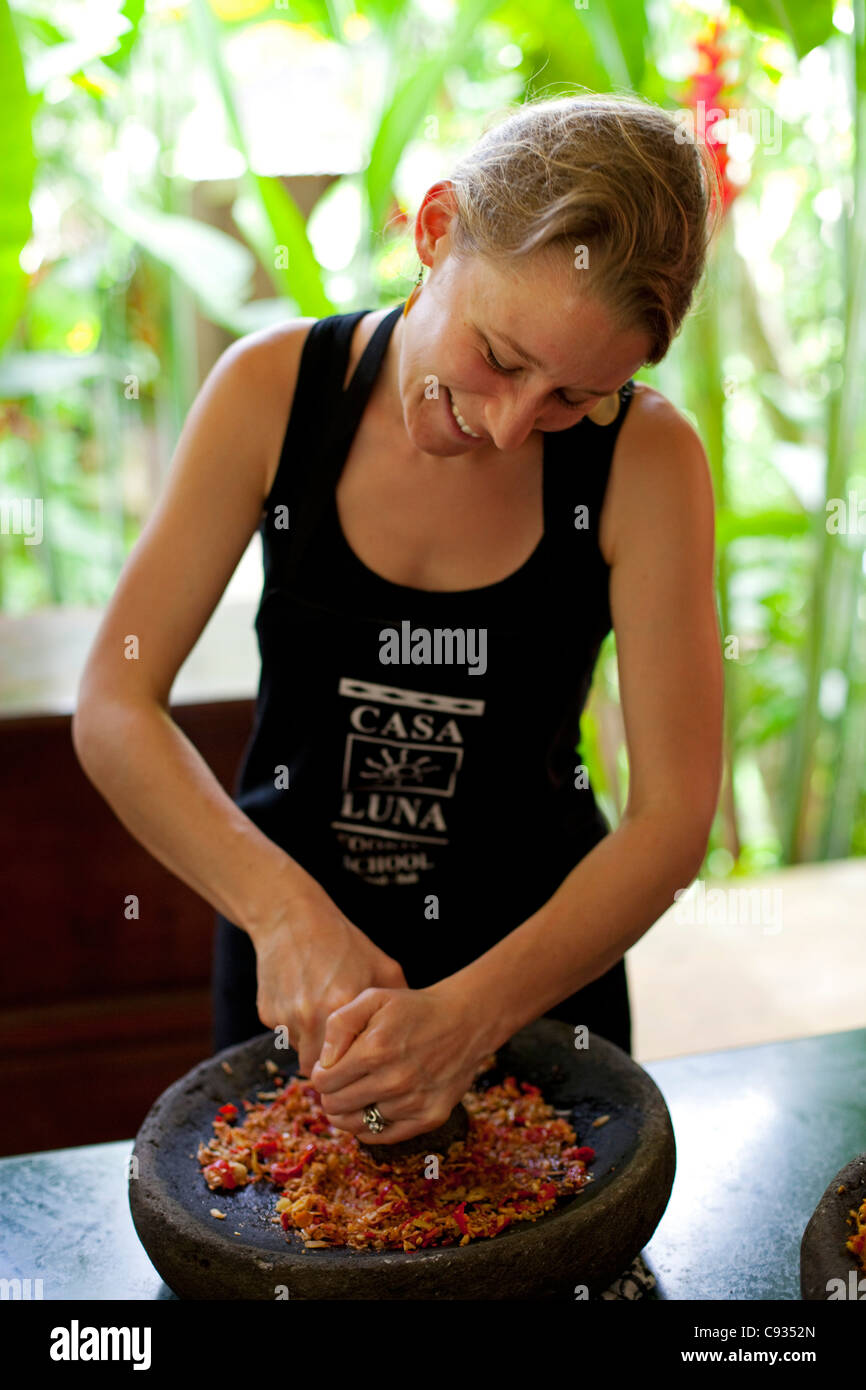 Bali, Ubud. A woman crushes ingredients at a cookery school. MR - Stock Image