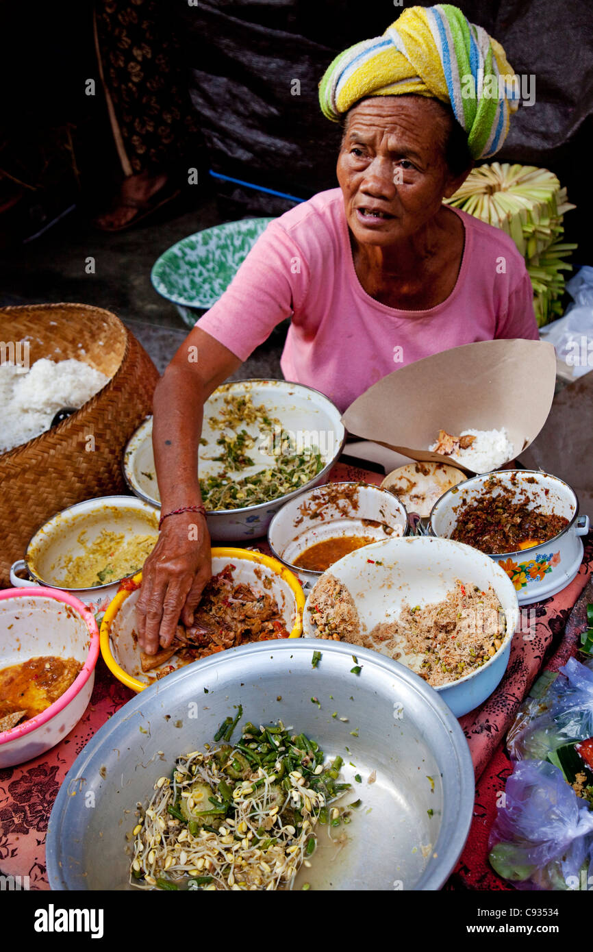 Bali, Ubud. A lady serves up traditional Balinese food for breakfast at an Ubud market. - Stock Image