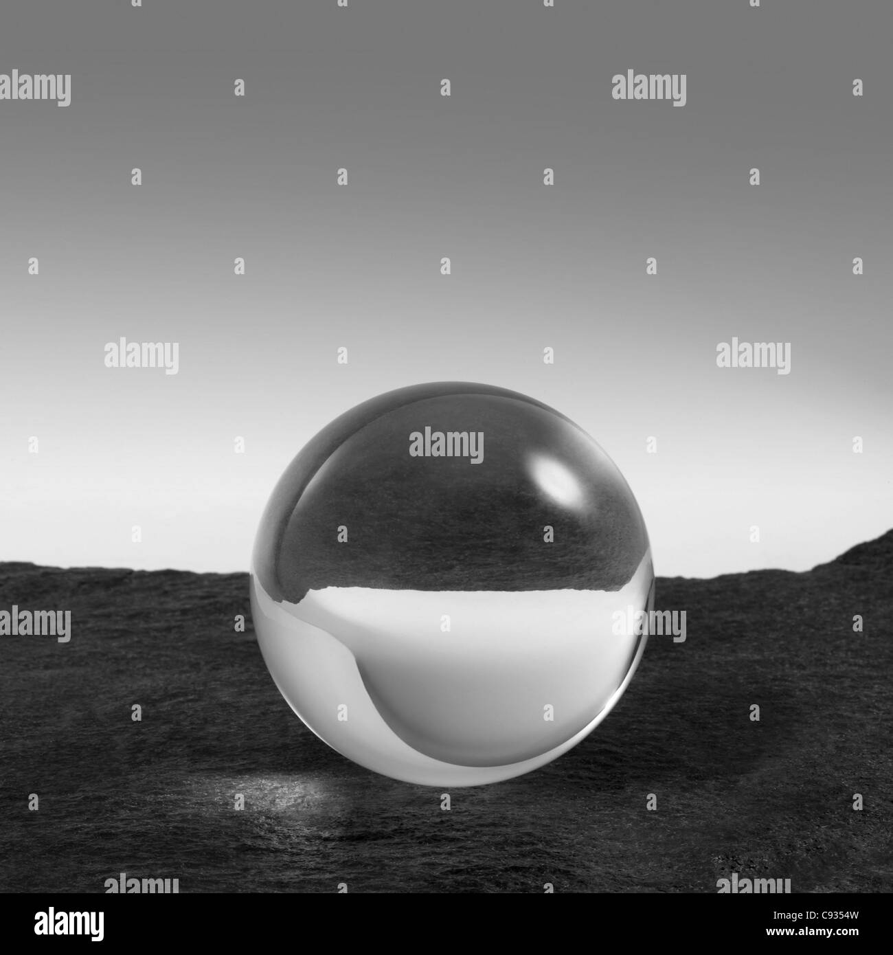 a clear crystal ball on rough dark grey stone surface in front of red back - Stock Image