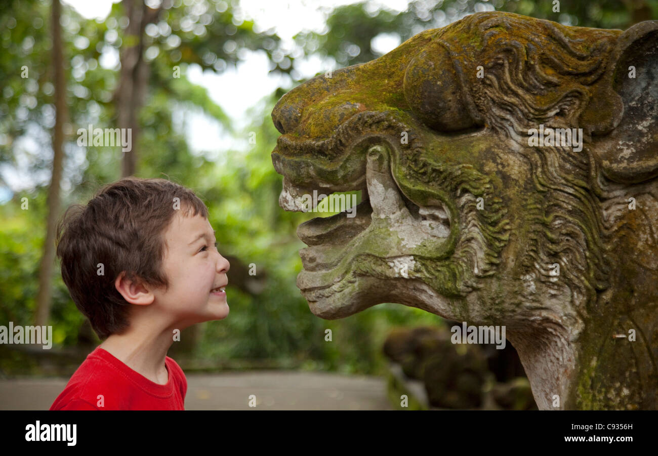 Bali, Ubud. A young tourist growls at an equally fierce stone carving in Ubud's Sacred Monkey Forest. MR - Stock Image