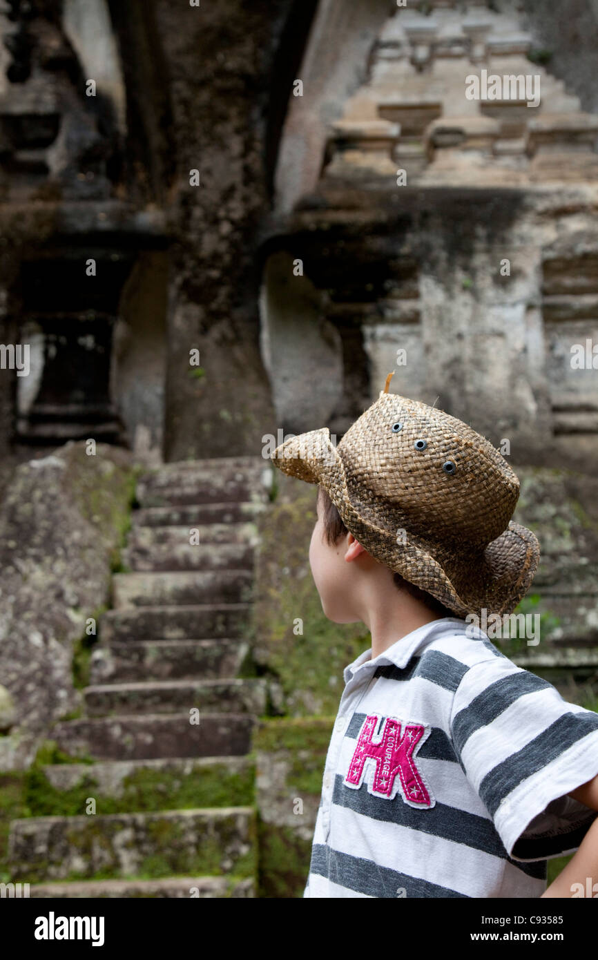 Bali, Ubud. A tourist gazes at the huge shrines carved out of the cliff-face at the Gunung Kawi Temples. MR - Stock Image
