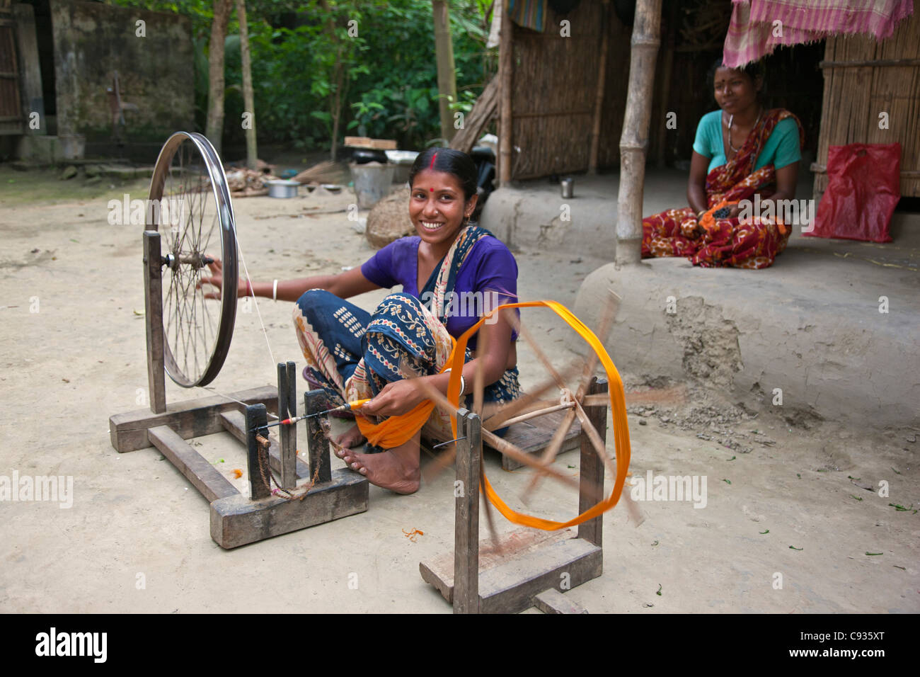 A woman spins silk onto bobbins at Santipur village on the banks of the Hooghly River. - Stock Image