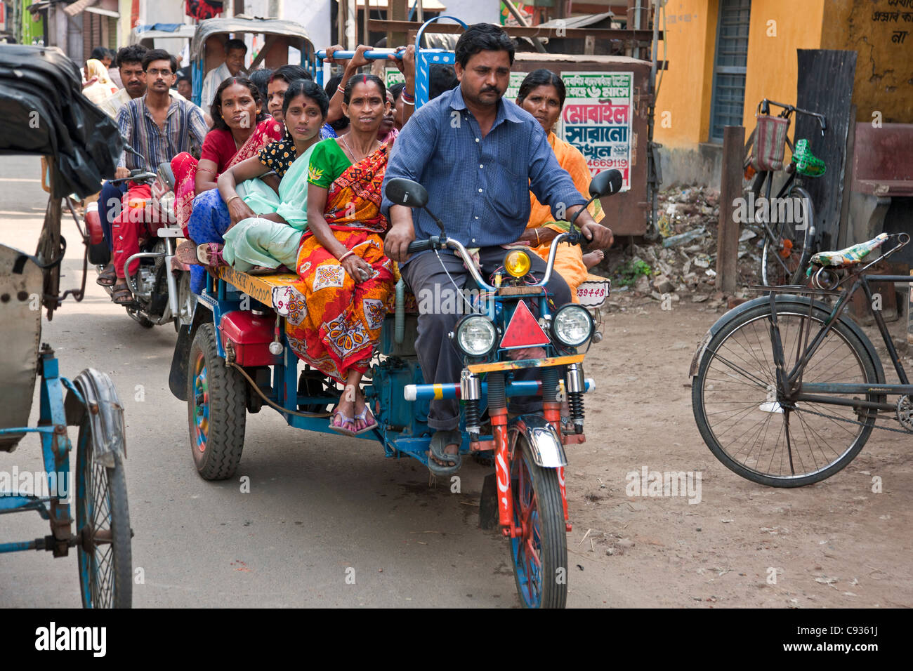 Crowded transport negotiates the narrow streets in Kalna. - Stock Image