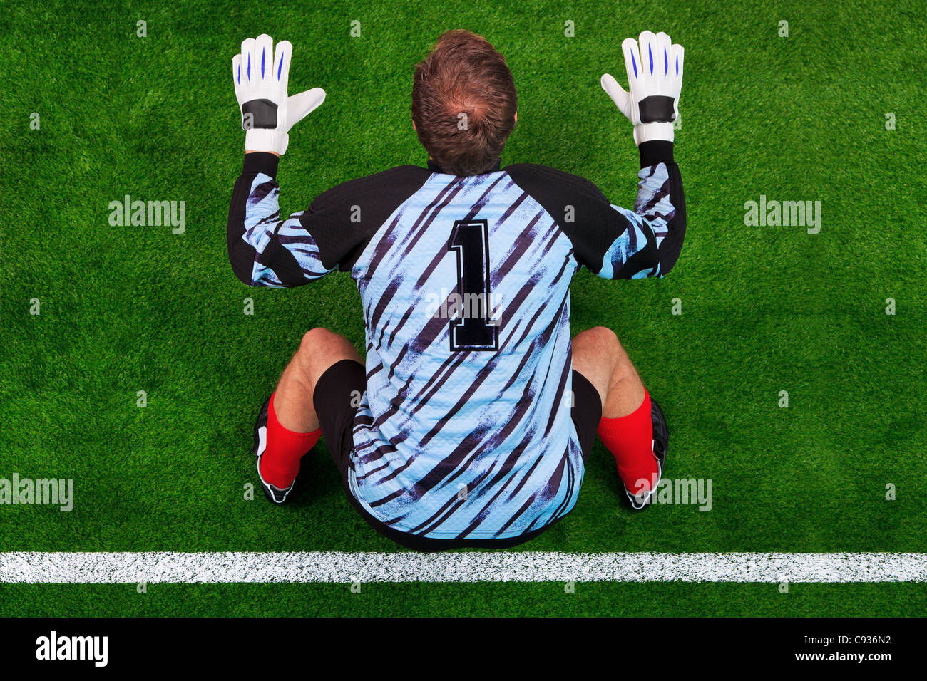 Overhead photo of a football goalkeeper standing on the goal line in ready position to face a penalty kick. - Stock Image