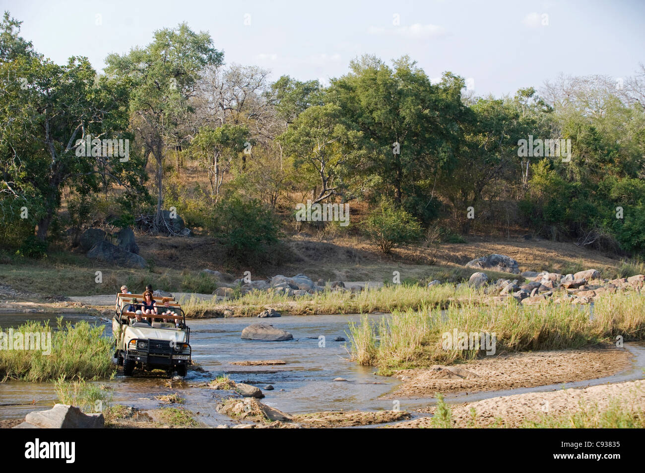 Malawi, Majete Wildlife Reserve.  Family on safari cross the Mkulumadzi River in their safari vehicle. - Stock Image