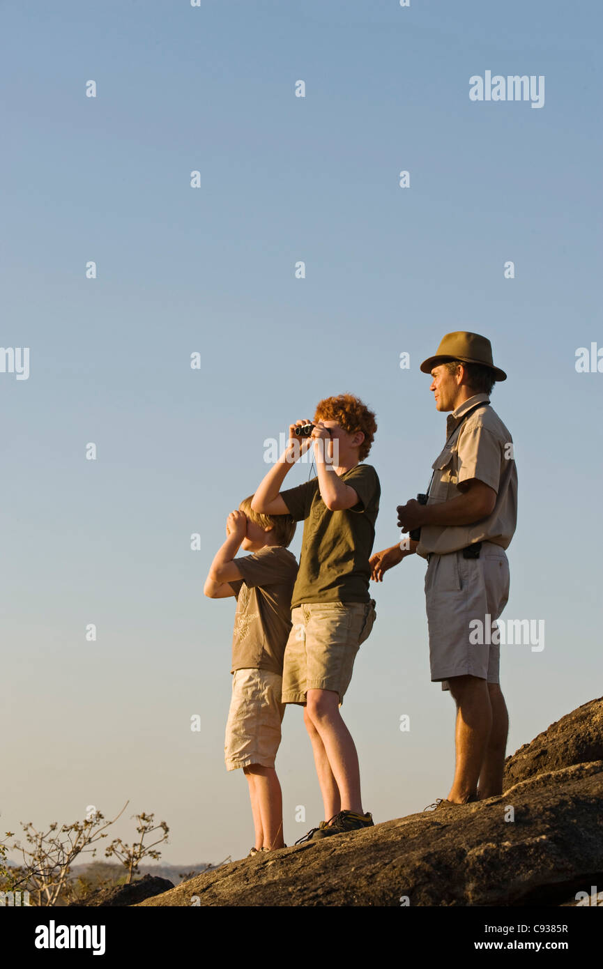 Malawi, Majete Wildlife Reserve. A guide with Robin Pope Safaris takes children on a family safari on a bush walk. - Stock Image