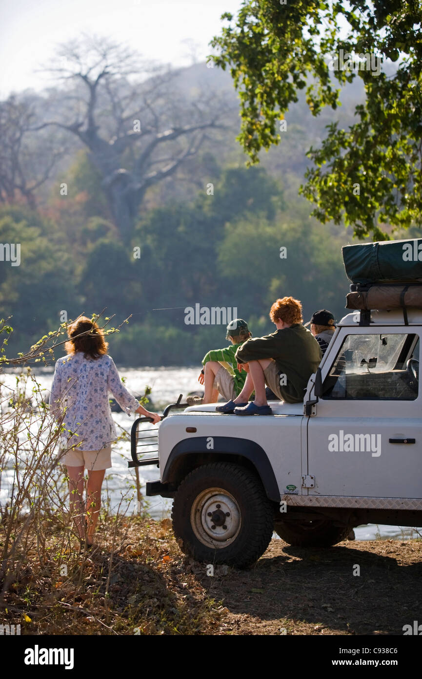 Malawi, Majete Wildlife Reserve.  Family on safari look out across the Shire River from their safari vehicle. MR - Stock Image