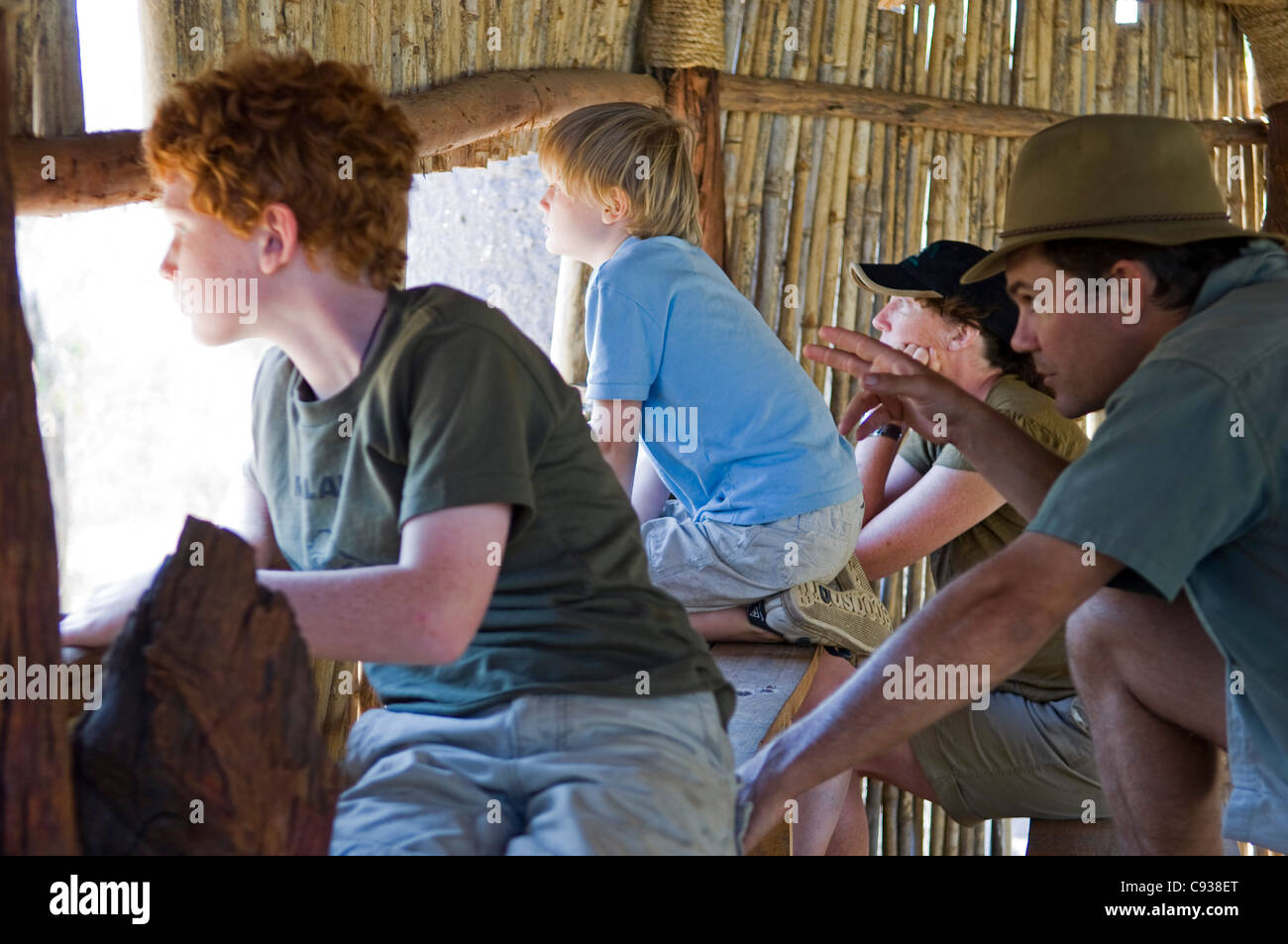 Malawi, Majete Wildlife Reserve.  Safari guide points out wildlife from a hide in Majete to a family  on safari. - Stock Image