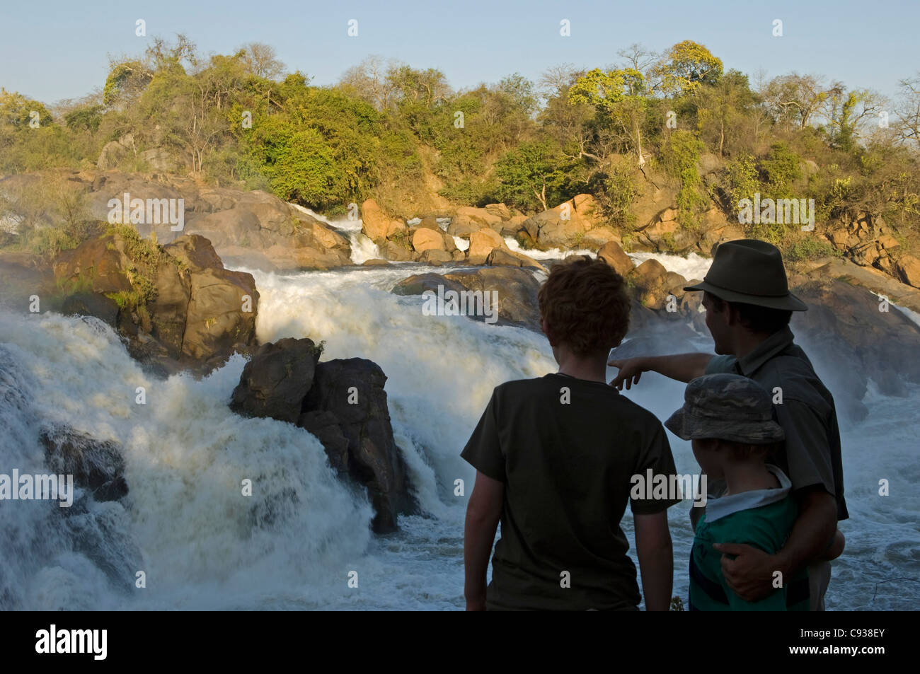 Malawi, Majete Wildlife Reserve.  A safari guide points out the Kapichira Falls to boys on a bush walk during a - Stock Image