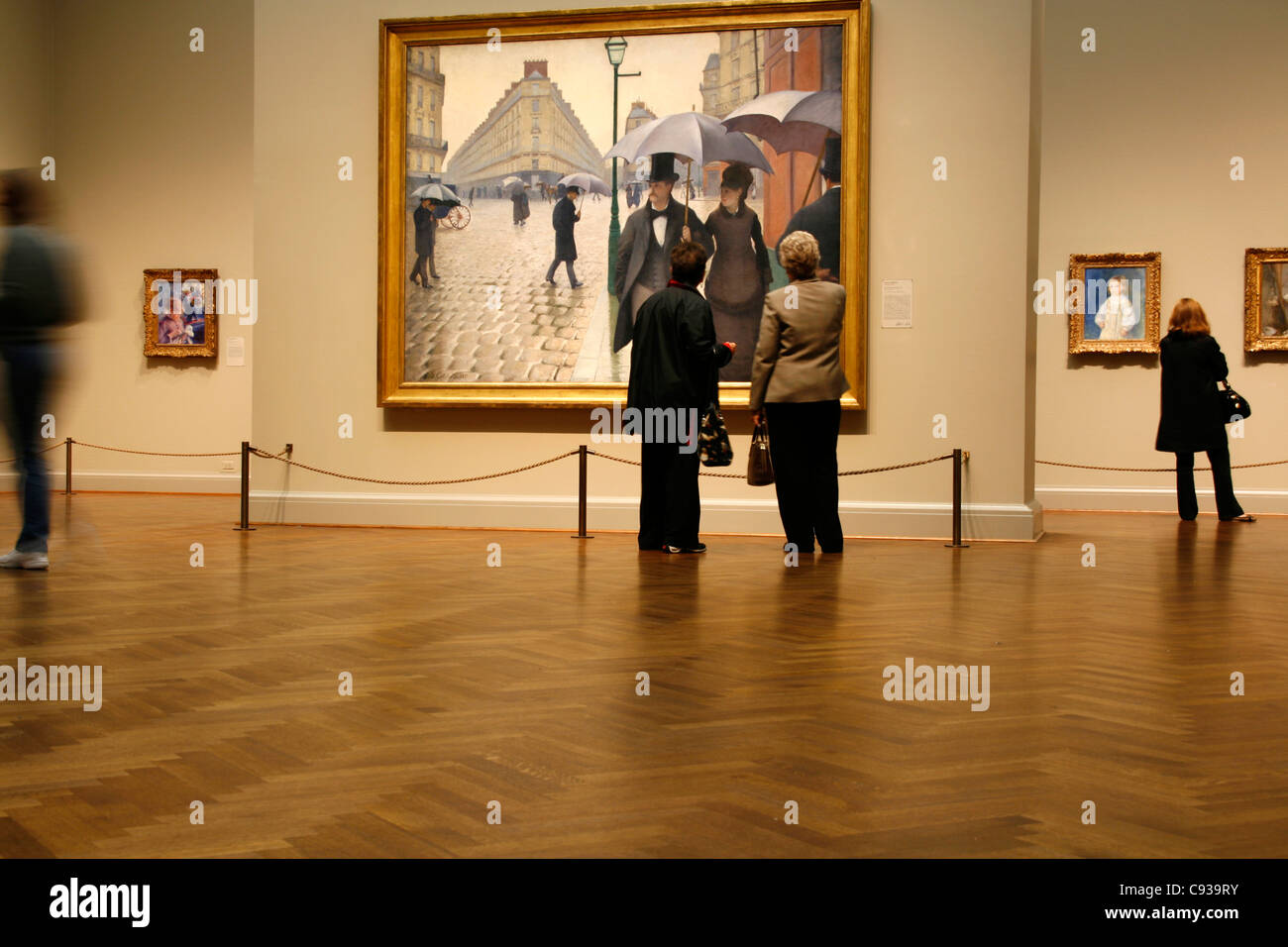 Visitors admiring the painting 'Jour de pluie à Paris' from Gustave Caillebotte in the Art Institute - Stock Image