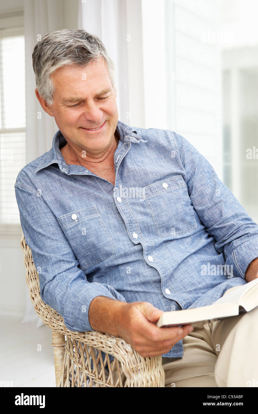 Senior man relaxing at home with a book - Stock Image