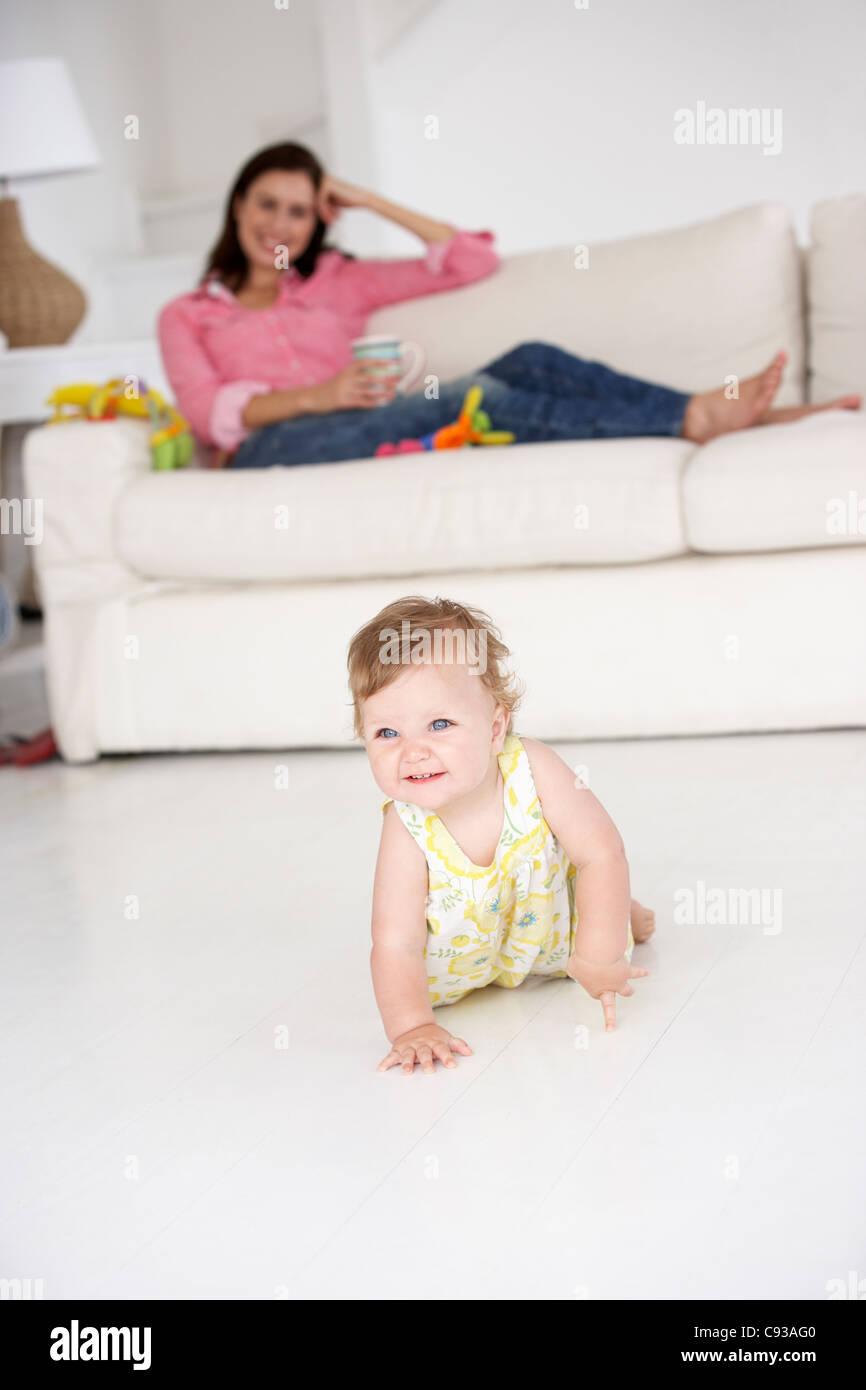Mother watching baby crawl - Stock Image