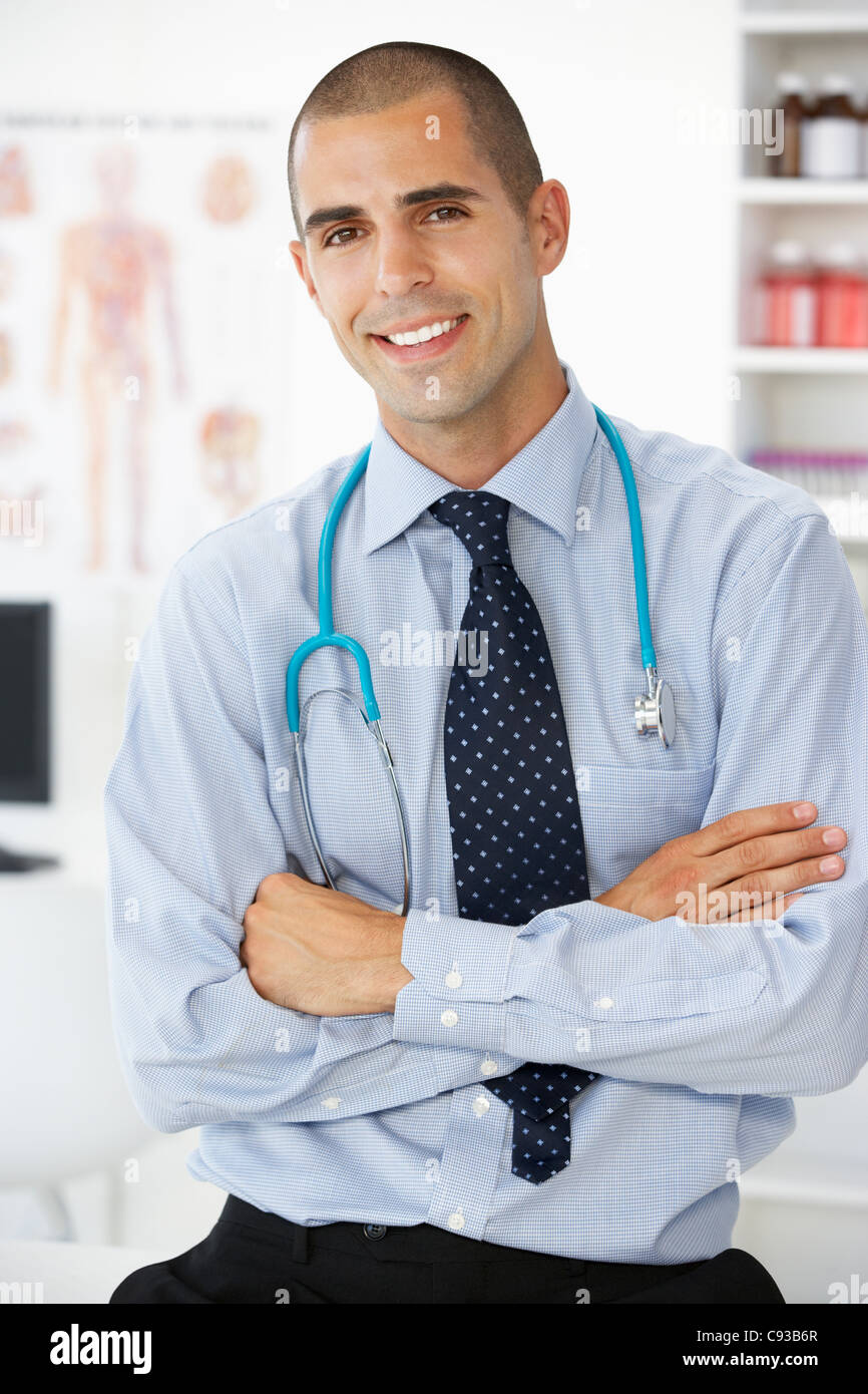 Young male doctor in consulting room - Stock Image