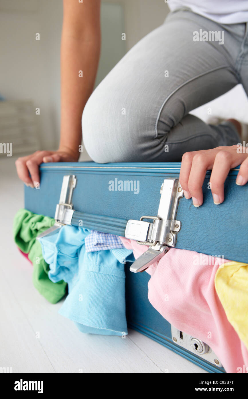 Teenage girl struggling to close suitcase Stock Photo