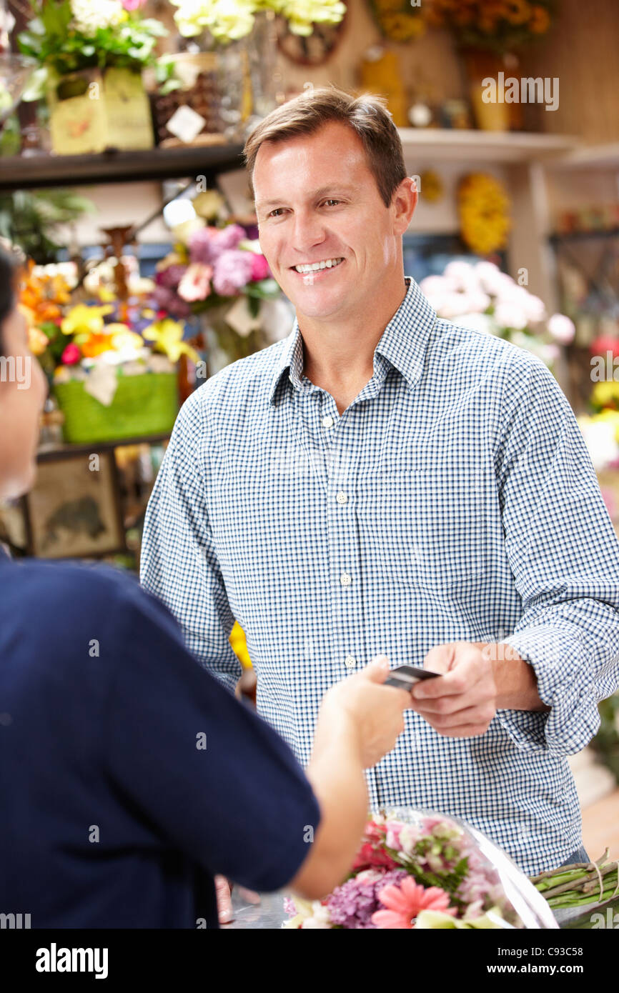 Man serving customer in florist - Stock Image