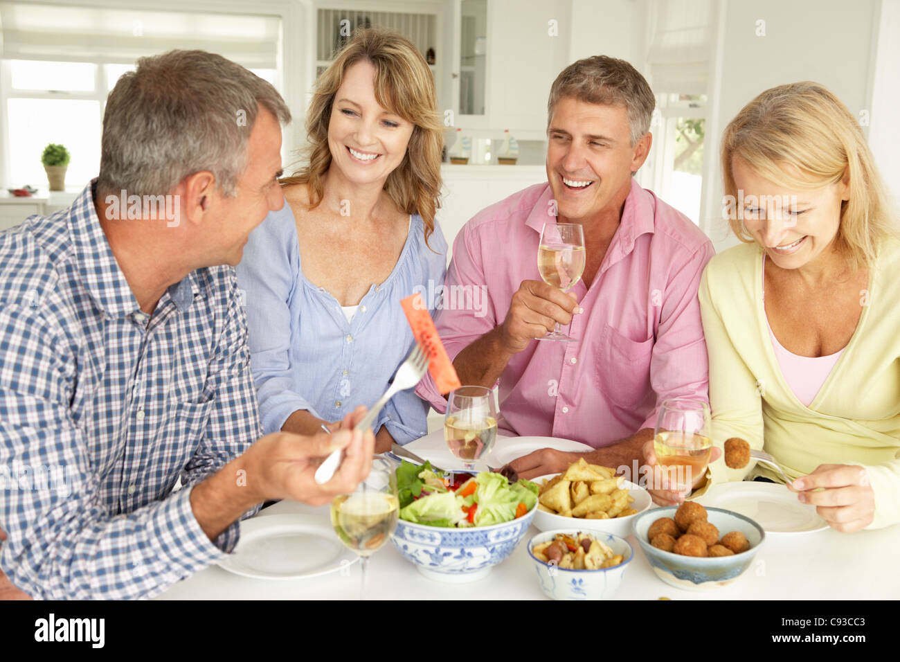 Mid age couples enjoying meal at home - Stock Image