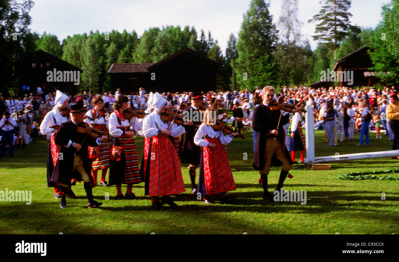 Fiddlers leading villagers at traditional Midsummer celebrations in Dalarna Sweden - Stock Image