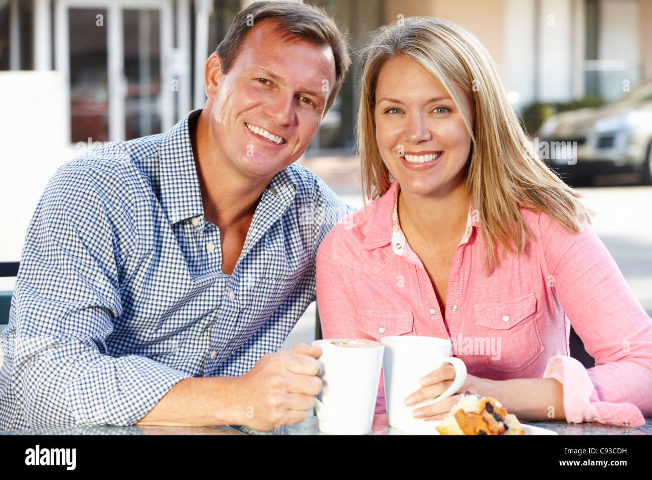 Couple sitting at sidewalk café Stock Photo