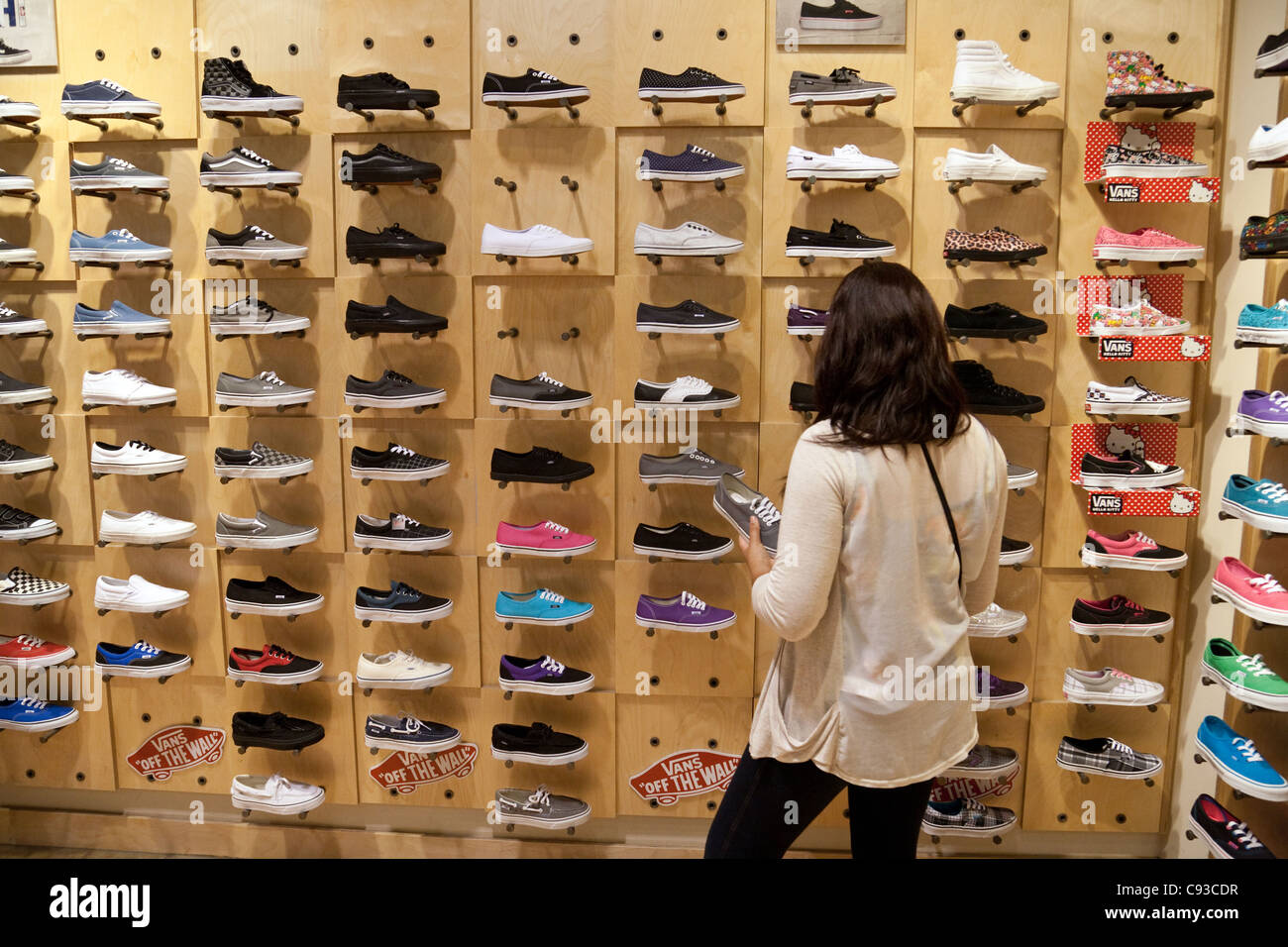 0625adfa336622 Teenage girl buying Vans shoes in a Vans Shoe shop