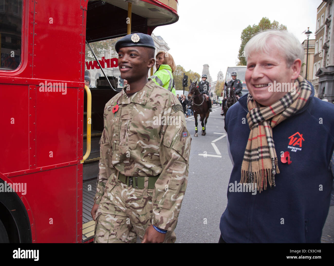 CEO of Veterans Aid Wg Cdr (Retd) Dr Hugh Milroy (right) walks alongside the bus with a member of the RAF Regiment. - Stock Image
