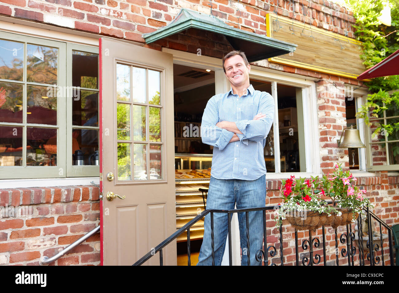 Man standing outside bakery/café Stock Photo