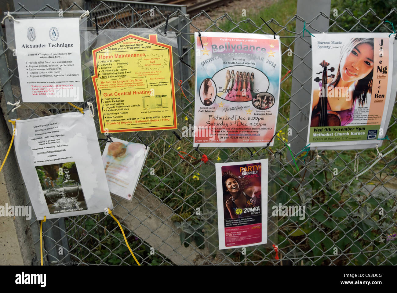 adverts for forthcoming events and courses fixed to a fence adjacent to a railway track in mortlake, southwest london, - Stock Image