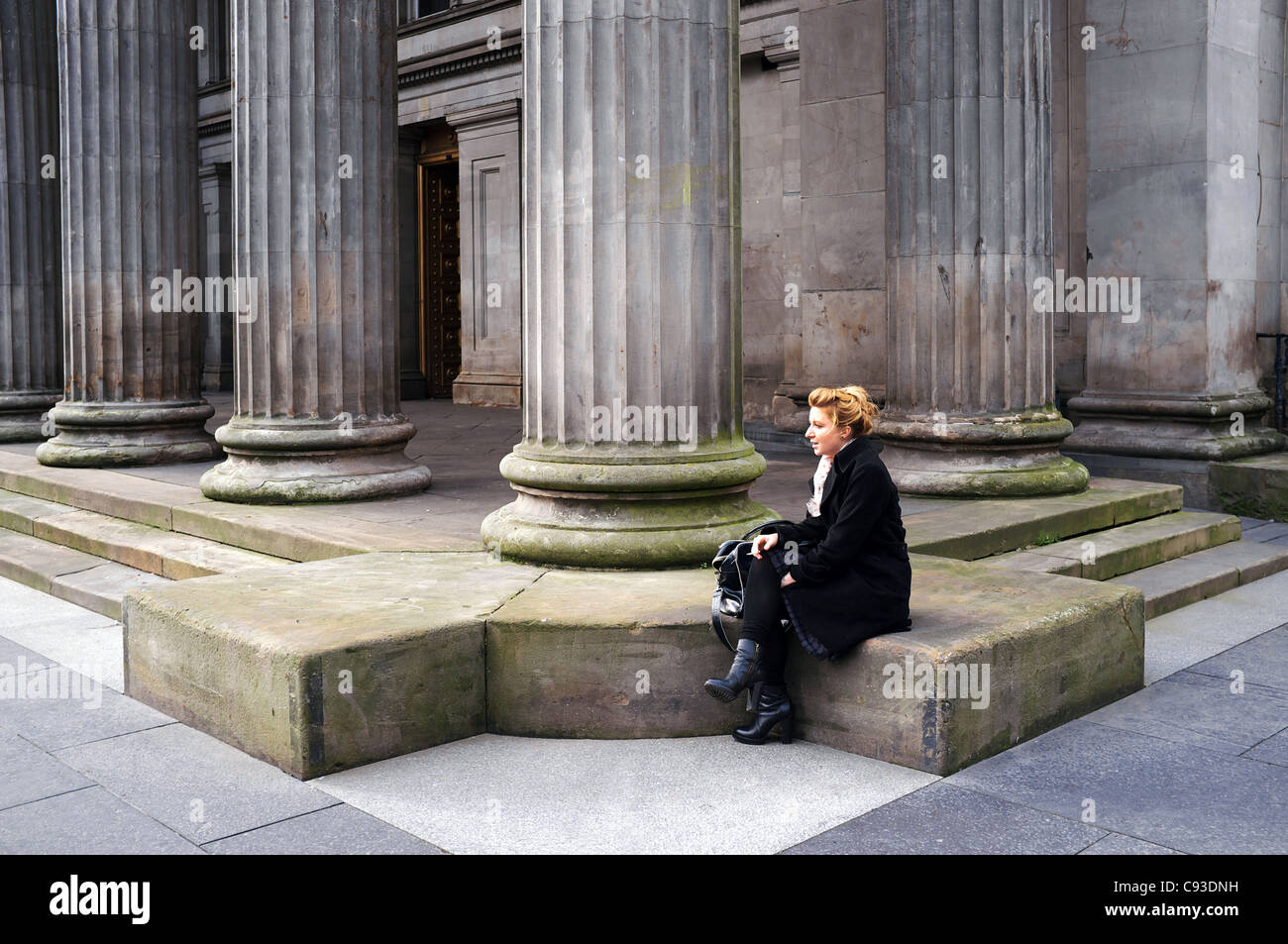 Woman sitting outside the Gallery of Modern Art, GOMA, Royal Exchange Square, Glasgow, Scotland, UK - Stock Image