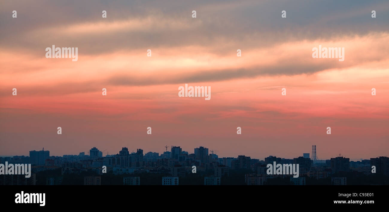 crimson sunset over big city, horizontal orientation - Stock Image