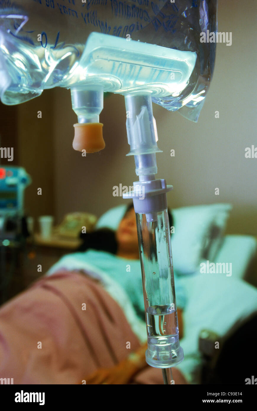 Female patient in hospital bed connected to IV - Stock Image