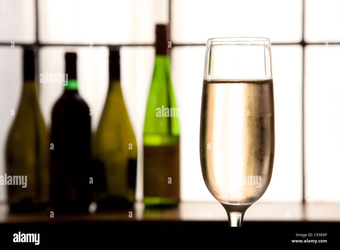 Glass of champagne in foreground with sepia tones and bottles in back ground. - Stock Image