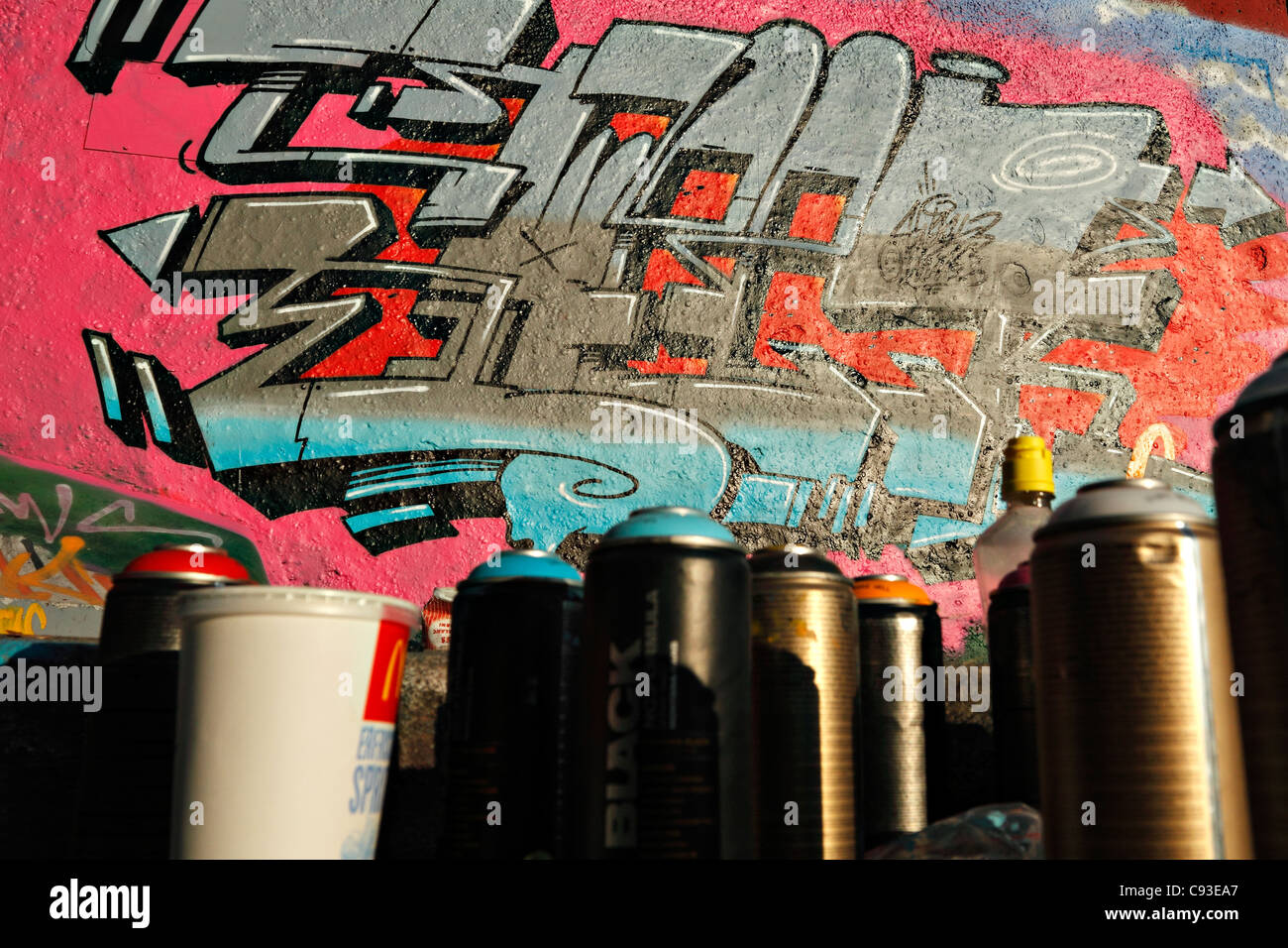 Spray Paint Cans And Graffiti On A Concrete Wall Under The