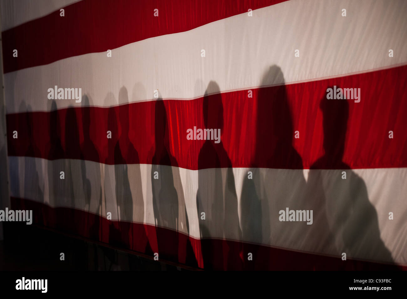 Shadows of Republican presidential candidate Michele Bachmann supporters on a giant flag during her foreign policy - Stock Image