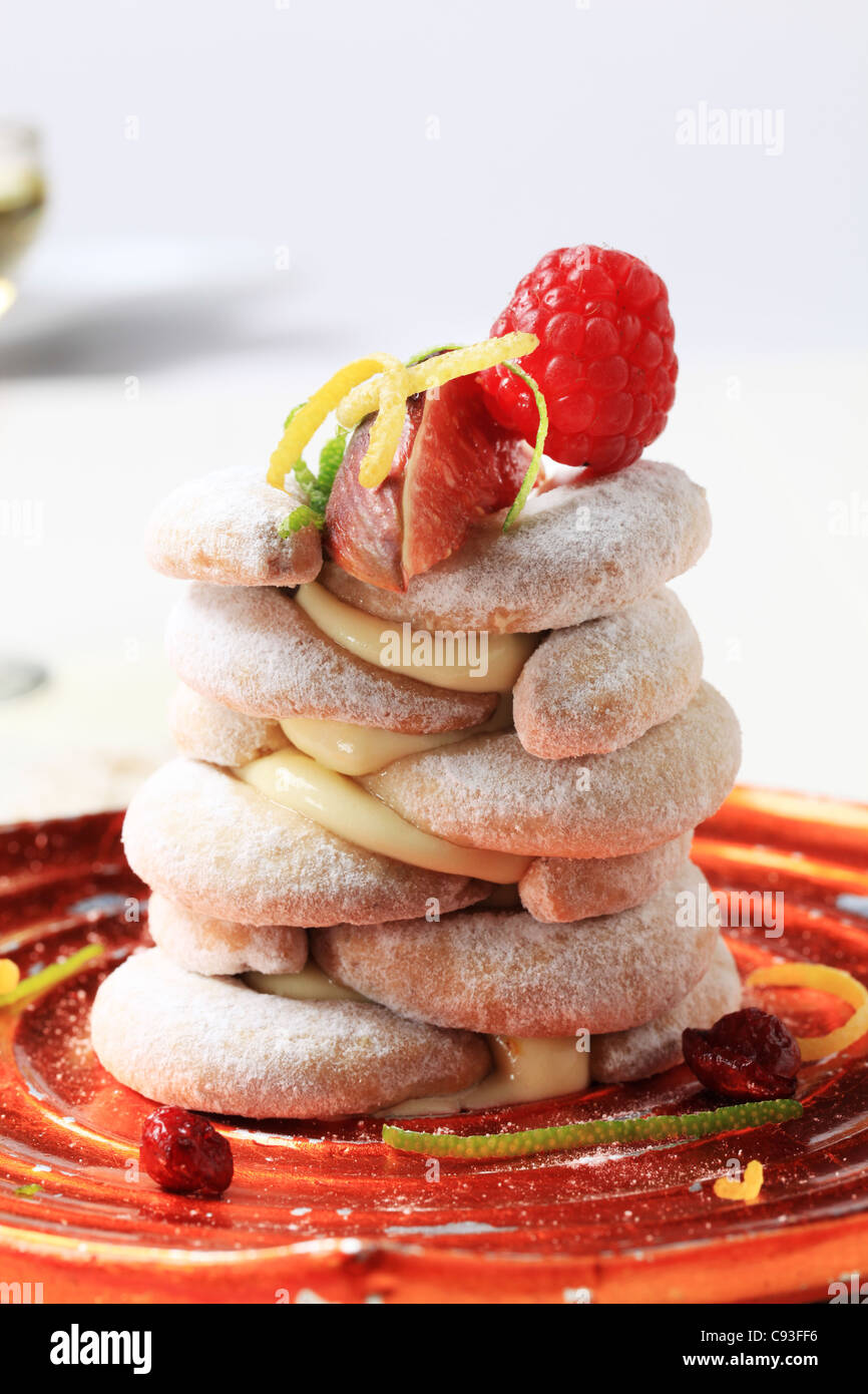 Crescent-shaped vanilla cookies with pudding and fruit - Stock Image