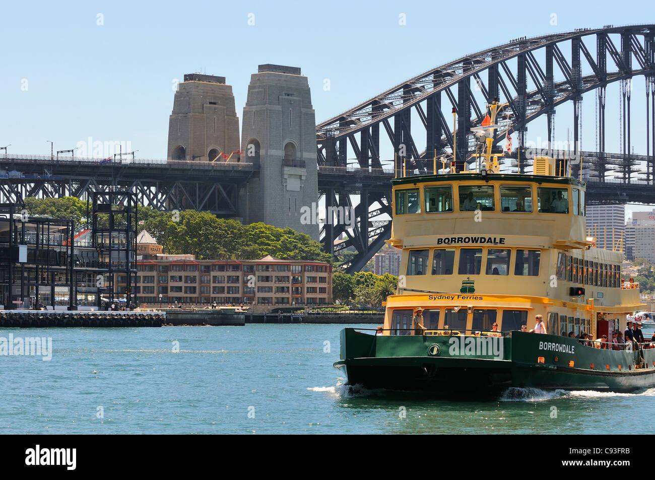 Sydney Ferry coming into Circular Quay terminal with Sydney Harbour bridge Overseas Passenger Terminal, Park Hyatt - Stock Image