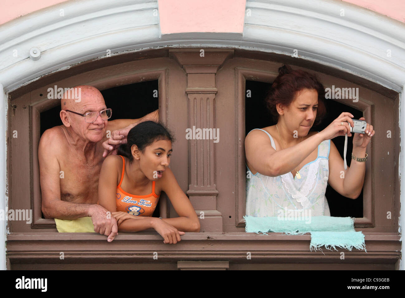 Cuban family looking from the window at a street procession in the historical centre of Havana, Cuba. Stock Photo