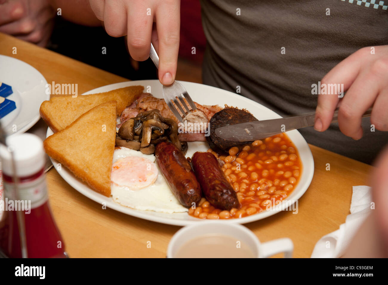 A 'greasy spoon' fried full english breakfast - bacon, egg, sausage, beans, fried bread, black pudding  - Stock Image